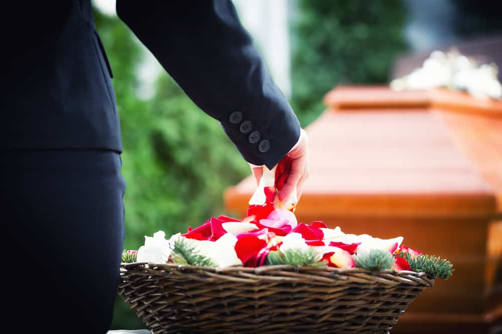 photo of funeral casket and a basket of flowers